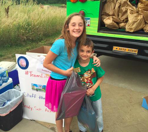 Two young kids in front of the bus after donating to Team Lisa