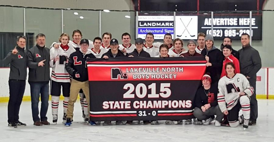 Members of the 2014-2015 state championship boys' hockey team stand with their new banner after the rout of Lakeville South