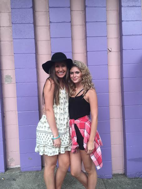 Killian wears her sun dress and floppy hat as she stands next to her friend