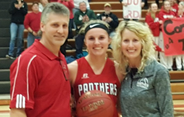 Carda stands with her parents immediately following her 1,000th point