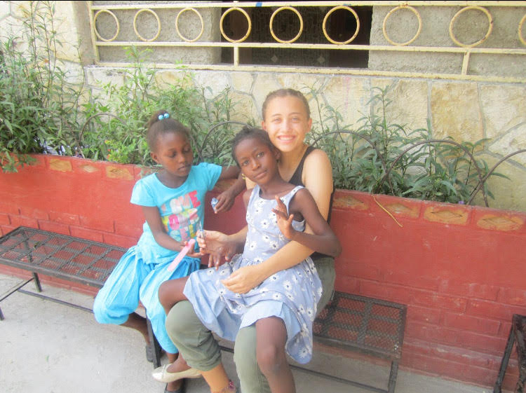 Abby+Russeth+sits+with+Haitian+children.+